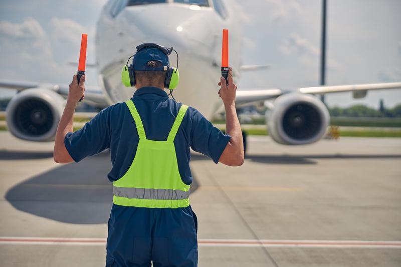 worker signally plane landing on runway